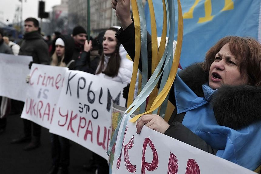 People hold placards reading 'Crimea is Ukraine' during a rally on Independence Square in central Kiev on March 1, 2014. Ukraine's acting president signed a decree on Saturday, March 1, 2014, declaring the appointment of a pro-Russia premier in the C