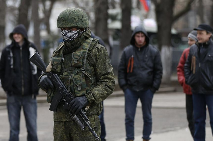 "An armed man patrols near the regional parliament building in the Crimean city of Simferopol, March 1, 2014. The Russian Foreign Ministry said on Saturday, March 1, 2014, that Moscow is ""extremely concerned"" about the recent developments in Ukra"