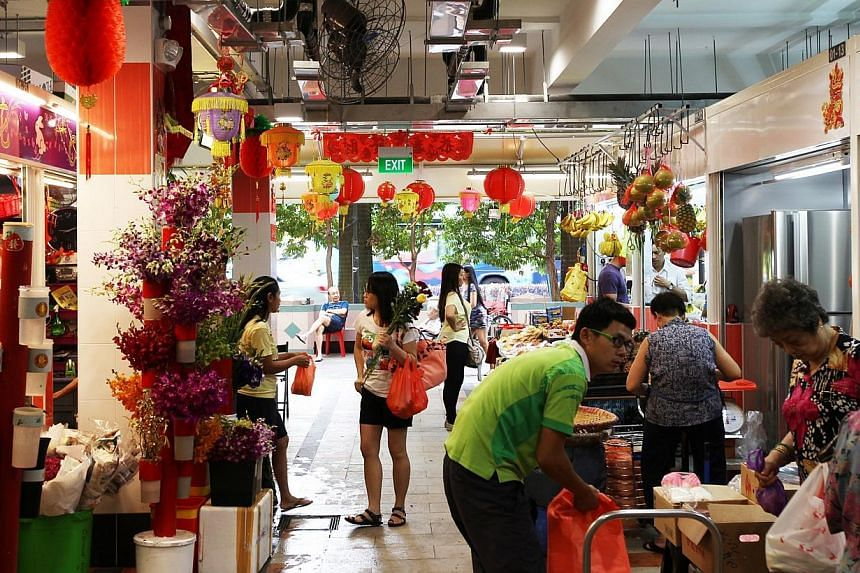 The Tanjong Pagar Plaza market and food centre re-opened officially on Saturday morning, March 1, 2014, with a bang, as a lion dance troupe leapt up on poles and a children's unicycling team performed.-- PHOTO: LIANHE ZAOBAO