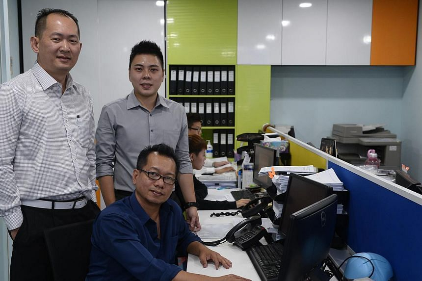 Ex-offender Shaharuddin Moktar (above) is now a chef at Royal Plaza on Scotts and was promoted twice in two years, while (left) IT associate Epin (seated), seen here with his company's executive chairman Fang Kok Look (far left) and head of HR Alvin