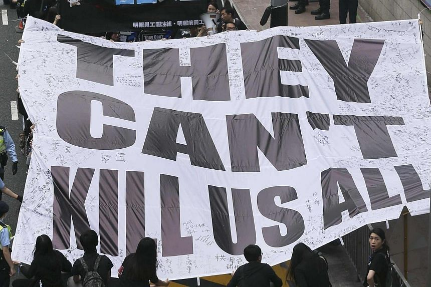 """Demonstrators carry a banner that reads """"They can't kill us all"""" during a march against violence on journalists in Hong Kong on Mar 2, 2014. -- PHOTO: REUTERS"""