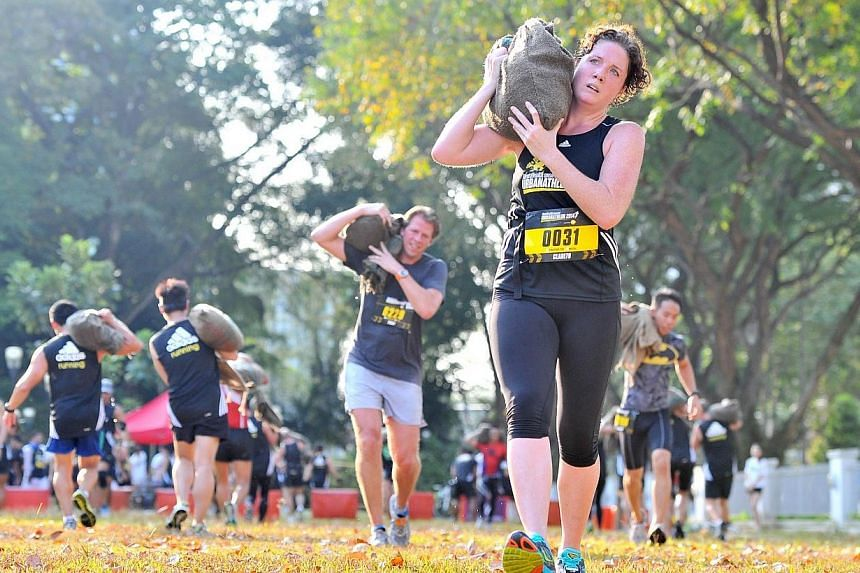 Participants carrying a wet 20kg sandbag and running 100m at obstacle 5, Workload, of The Men's Health Urbanathlon at Lawn @ Foothills on Mar 2, 2014. -- ST PHOTO: LIM YAOHUI
