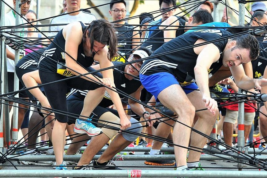 Participants untangling themselves in 4m long web of bungee cords at obstacle 2, Wire House, of The Men's Health Urbanathlon at Cavenagh Bridge on Mar 2, 2014. -- ST PHOTO: LIM YAOHUI