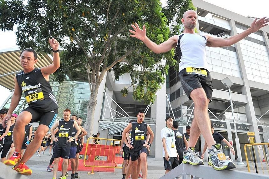 Participants balancing themselves across 2-inch wide beams at obstacle 1, Balance Sheet, of The Men's Health Urbanathlon at MBS Event Square on Mar 2, 2014. -- ST PHOTO: LIM YAOHUI