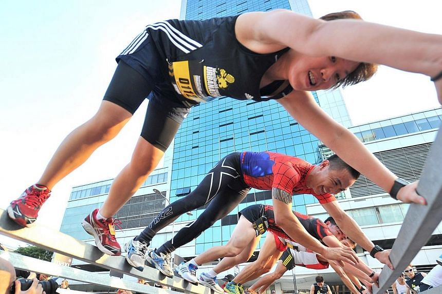Participants moving across 2 sets of parallel bars at obstacle 3, Lateral Move, of The Men's Health Urbanathlon at North Boat Quay on Mar 2, 2014. -- ST PHOTO: LIM YAOHUI