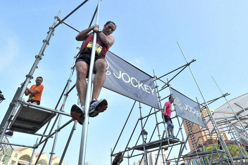 Participants taking a 2m leap of faith at obstacle 7, Leap of Faith, of The Men's Health Urbanathlon at Read Bridge on Mar 2, 2014. -- ST PHOTO: LIM YAOHUI