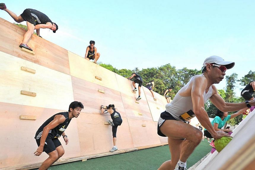 Participants scaling up and descending 3m high sloping structures at obstacle 4, Peaks and Troughs, of The Men's Health Urbanathlon at Fort Canning Green on Mar 2, 2014. -- ST PHOTO: LIM YAOHUI