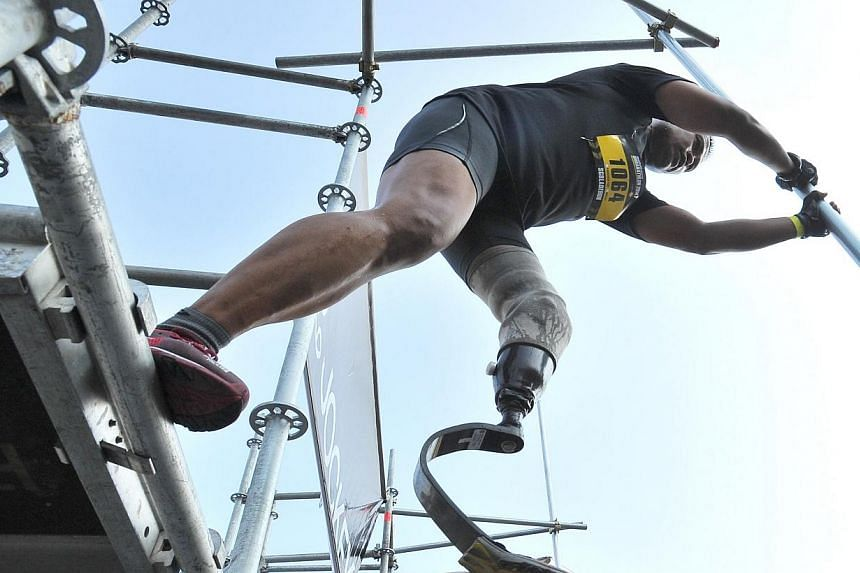 "Singapore's ""Blade Runner"" Mohd Shariff Abdullah taking a 2m leap of faith at obstacle 7, Leap of Faith, of The Men's Health Urbanathlon at Read Bridge on Mar 2, 2014. -- ST PHOTO: LIM YAOHUI"