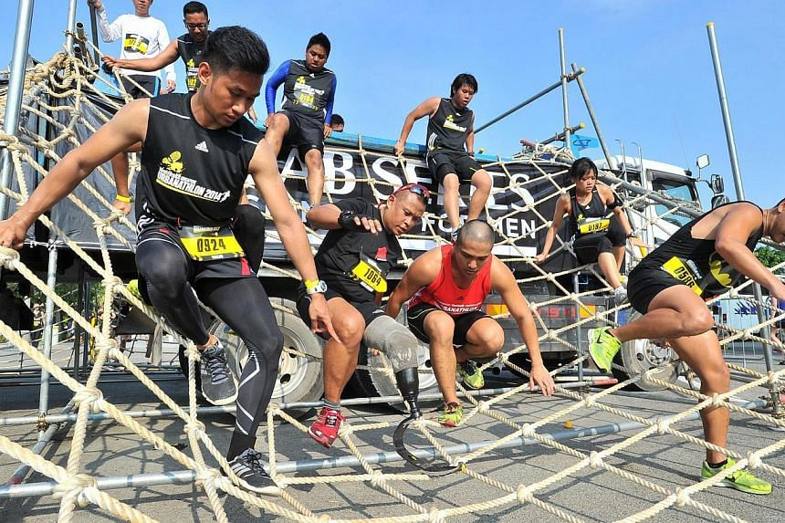 """Participants, including Singapore's """"Blade Runner"""" Mohd Shariff Abdullah (tag 1064), climbing up and down a 3.2m high 3-ton truck using rope web at obstacle 8, The Network, of The Men's Health Urbanathlon at F1 Turn 16/17 on Mar 2, 2014. -- ST PHOTO:"""
