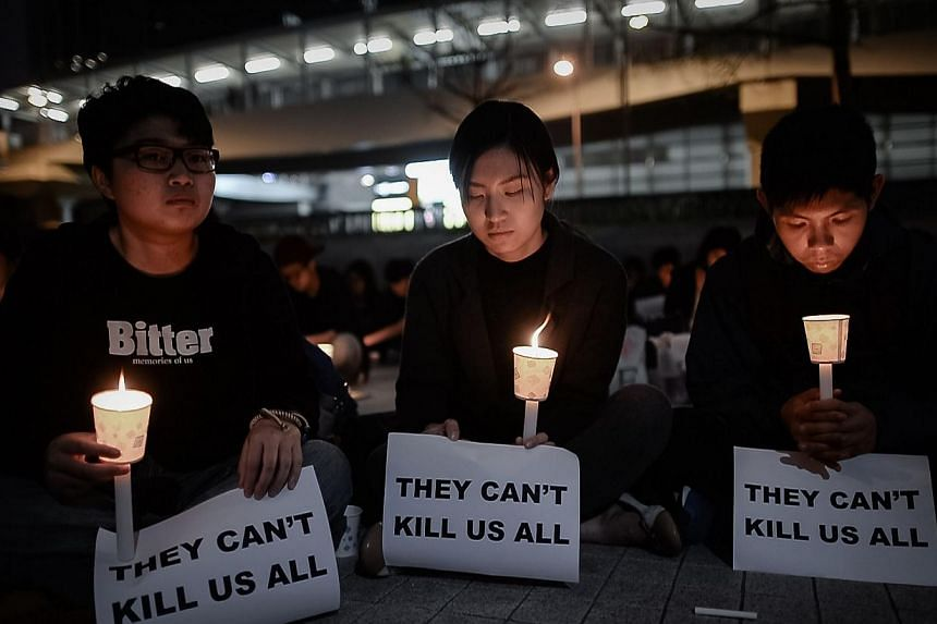 Protesters hold candles during a demonstration in support of the former editor of a liberal Hong Kong newspaper who was stabbed in Hong Kong on Feb 27, 2014. -- PHOTO; AFP
