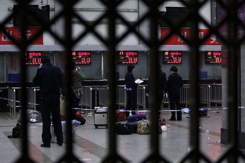 """Police investigators inspect the scene inside the Kunming railway station after an attack in Kunming, southwest China's Yunnan province on Mar 2, 2014.China will spare no effort to seek justice for a """"terrorist attack"""" at a crowded train statio"""