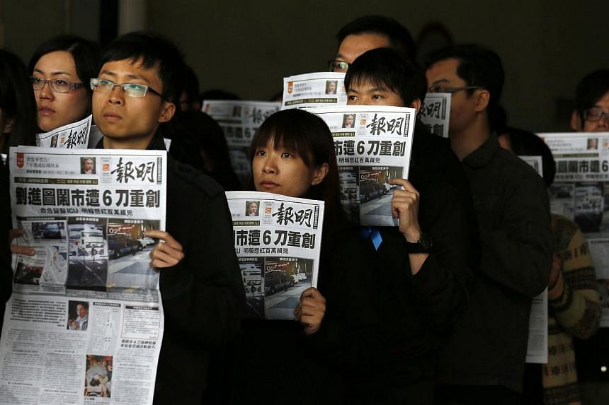 Journalists and editors from Ming Pao hold up front pages of their newspaper during a protest against violence in Hong Kong on Feb 27, 2014, after Wednesday's attack on their former chief editor Kevin Lau. -- PHOTO: REUTERS