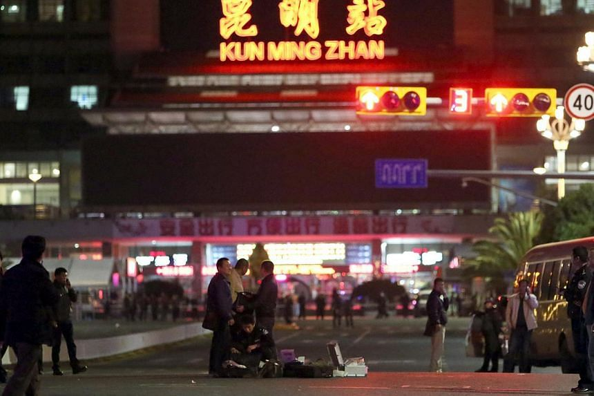 Chinese police investigators inspect the scene of an attack outside the railway station in Kunming, south-west China's Yunnan province, on March 2, 2014. -- PHOTO: AFP