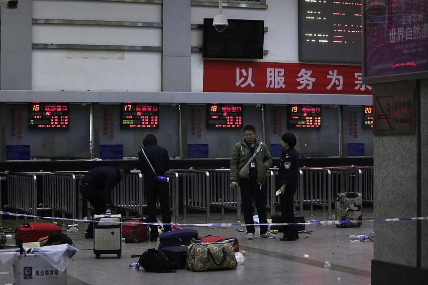 Police stand near luggages left at the ticket office after a group of armed men attacked people at Kunming railway station, Yunnan province, on March 2, 2014. -- PHOTO: REUTERS