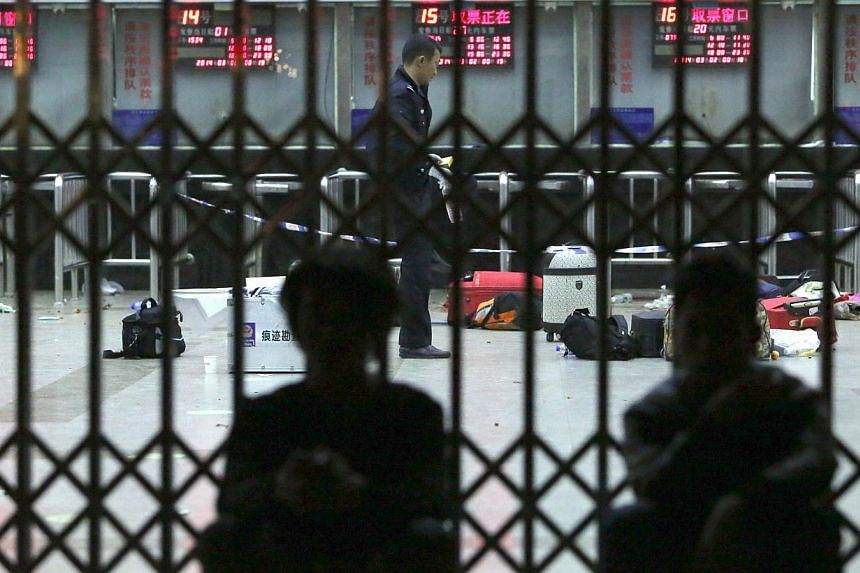Chinese police investigators inspect the scene of an attack at the railway station in Kunming, south-west China's Yunnan province, on March 2, 2014. -- PHOTO: AFP