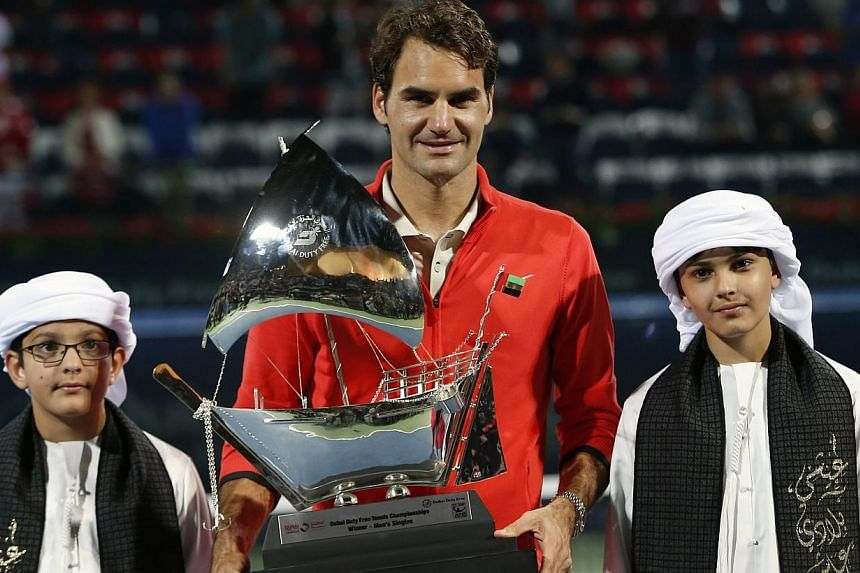 Roger Federer of Switzerland poses with the trophy as he stands between Emirati boys after defeating Tomas Berdych of Czech Republic in their men's singles final match at the ATP Dubai Tennis Championships on March 1, 2014. -- PHOTO: REUTERS