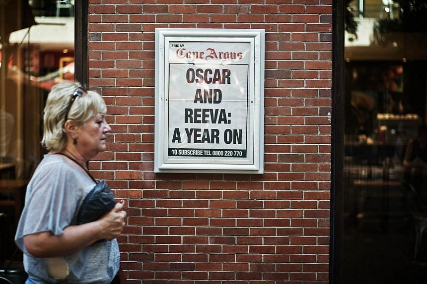 A woman walks by a newspaper advertising placard marking the anniversary of the killing of South African model Reeva Steenkamp by her boyfriend, Olympic athlete Oscar Pistorius on Mar 14, 2014 in Cape Town, South Africa. -- FILE PHOTO: AFP