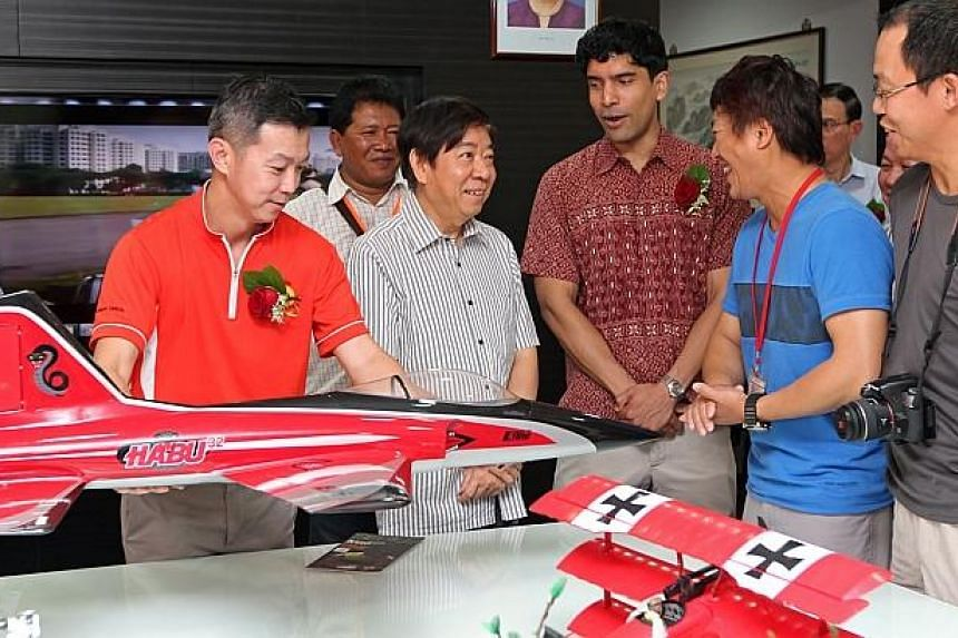 Dr Lim Wee Kiak (MP for Nee Soon GRC) (left), Minister Khaw Boon Wan (centre), Mr Vikram Nair (MP for Sembawang GRC, right) talk to members of the aero modelling interest group in the conference room of new the new 4-storey Ace the Place Community Cl