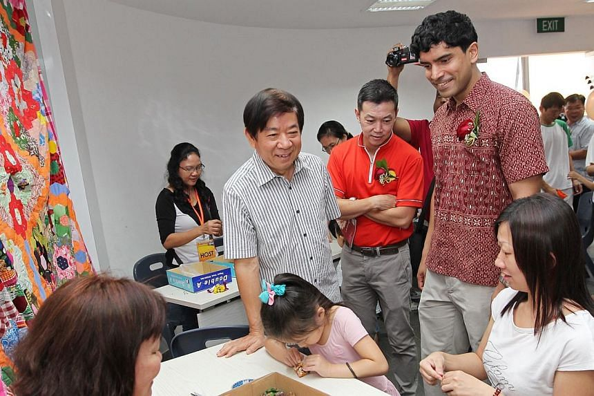 """(from left) Minister Khaw Boon Wan, Dr Lim Wee Kiak (MP for Nee Soon GRC) and Mr Vikram Nair (MP for Sembawang GRC, right) interacts with residents sewing """"5-stones"""" in an activity room of new 4-storey Ace the Place Community Club.-- ST PHOTO:&"""