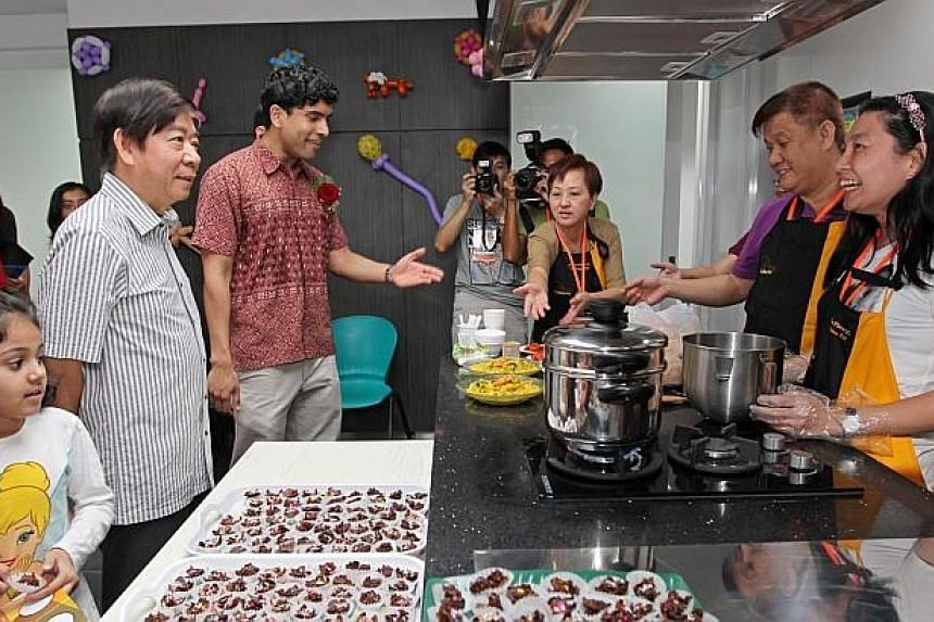 Minister Khaw Boon Wan (left) and Mr Vikram Nair (Grassroots Adviser to Admiralty GROs) speaks to residents who baked pastries in the community kitchen of the new 4-storey Ace the Place Community Club. -- ST PHOTO: SEAH KWANG PENG