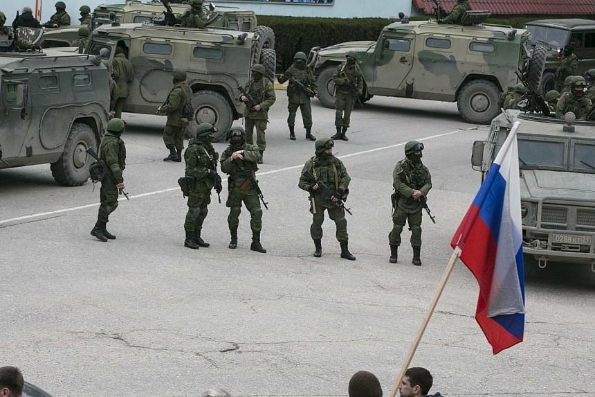 Pro-Russian men hold Russian flags in front of armed servicemen near Russian army vehicles outside a Ukrainian border guard post in the Crimean town of Balaclava on March 1, 2014. President Vladimir Putin has not yet decided whethe to deploy Russian