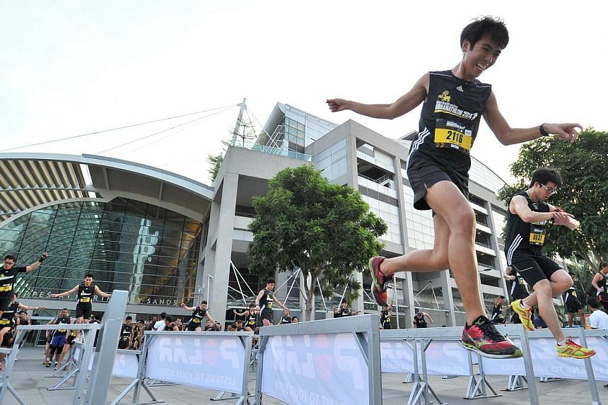 Participants balancing themselves across 2-inch wide beams at obstacle 1, Balance Sheet, of The Men's Health Urbanathlon at MBS Event Square on Mar 02 2014. -- PHOTO: LIM YAOHUI FOR THE STRAITS TIMES