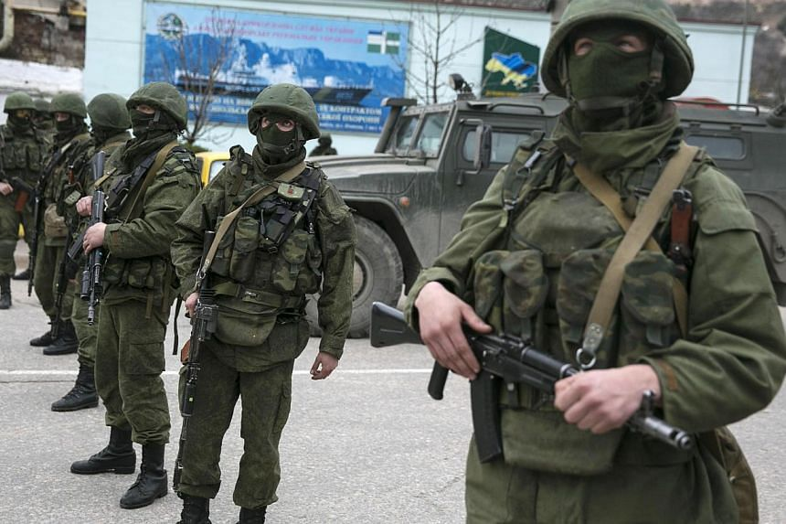 Armed servicemen stand near Russian army vehicles outside a Ukrainian border guard post in the Crimean town of Balaclava on March 1, 2014. -- PHOTO: REUTERS
