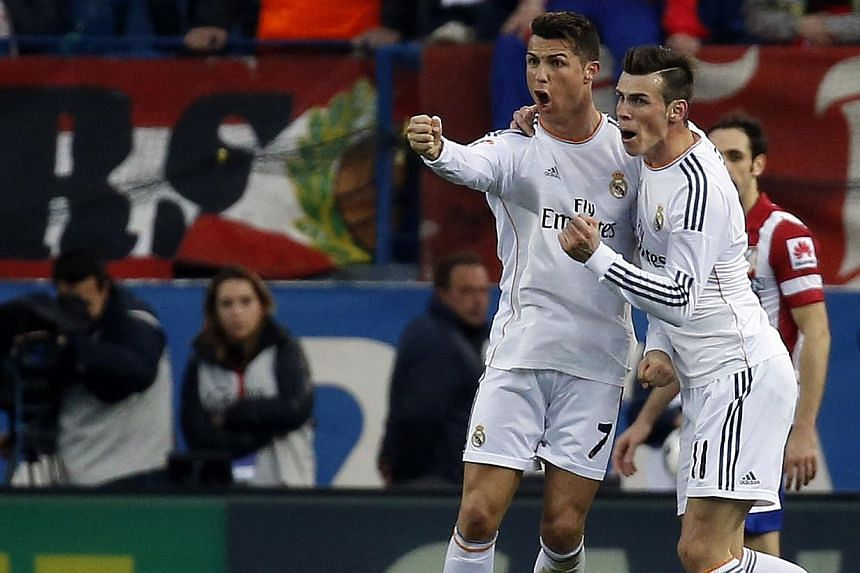 Real Madrid's Cristiano Ronaldo (left) celebrates his goal with teammate Gareth Bale after scoring a goal in their Spanish first division soccer match at Vicente Calderon stadium in Madrid on Mar 2, 2014. -- PHOTO: REUTERS