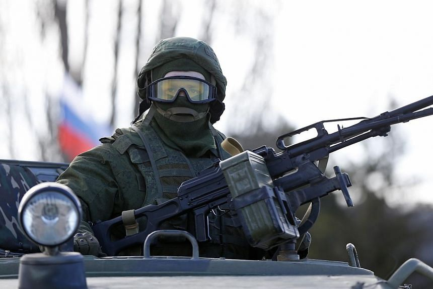 A military personnel member, believed to be a Russian serviceman, stands guard on a military vehicle outside the territory of a Ukrainian military unit in the village of Perevalnoye outside Simferopol on Mar 3, 2014. -- PHOTO: REUTERS