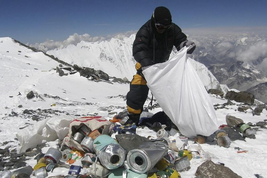 This picture taken on May 23, 2010 shows a Nepalese sherpa collecting garbage, left by climbers, at an altitude of 8,000 metres during the Everest clean-up expedition at Mount Everest. Climbers scaling Mount Everest will have to bring back eight kilo