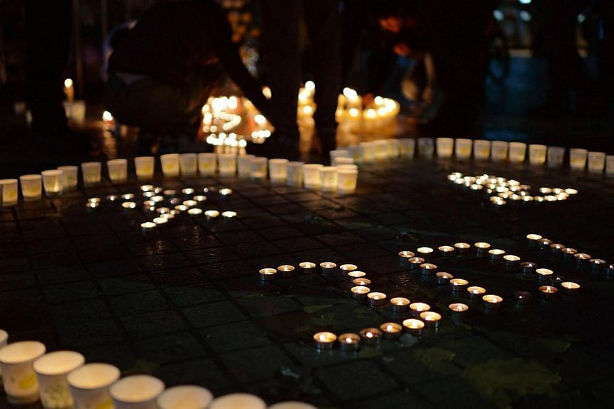 This picture taken on March 2, 2014 shows Chinese mourners lighting candles at the scene of the terror attack at the main train station in Kunming, south-west China's Yunnan Province. Chinese Internet users on Monday, March 3, 2014, accused the Unite