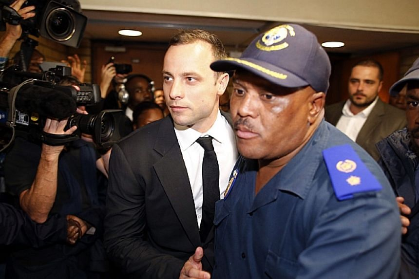 South African Paralympian star Oscar Pistorius (centre left) leaves the court after the first day of his trial on March 3, 2014 in Pretoria. -- PHOTO: AFP