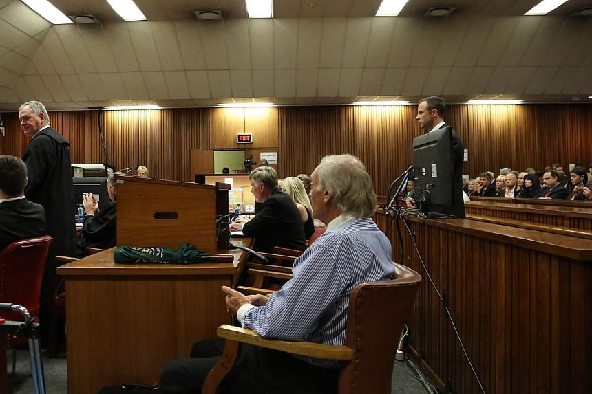 Oscar Pistorius's lawyer Barry Roux (left), speaks at the start of Pistorius' (right) trial at the High Court in Pretoria on March 3, 2014 on the opening day of his murder trial, accused of murdering his girlfriend Reeva Steenkamp. The first witness