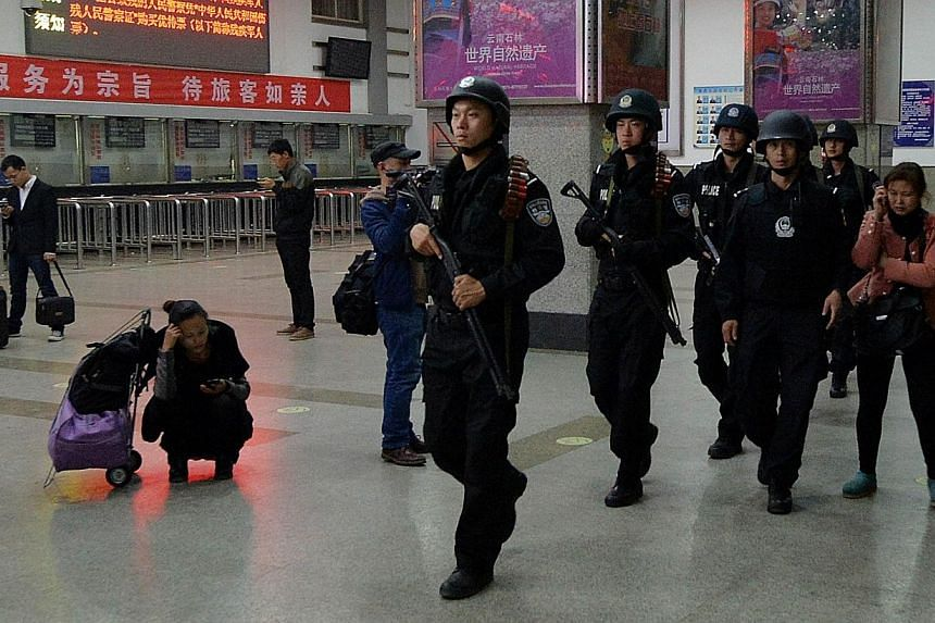 Chinese armed police patrol the scene of the terror attack at the main train station in Kunming, Yunnan Province on March 2, 2014. Singapore on Monday, March 3, 2014, strongly condemned the mass-stabbing attacks in China's south-western city of Kunmi