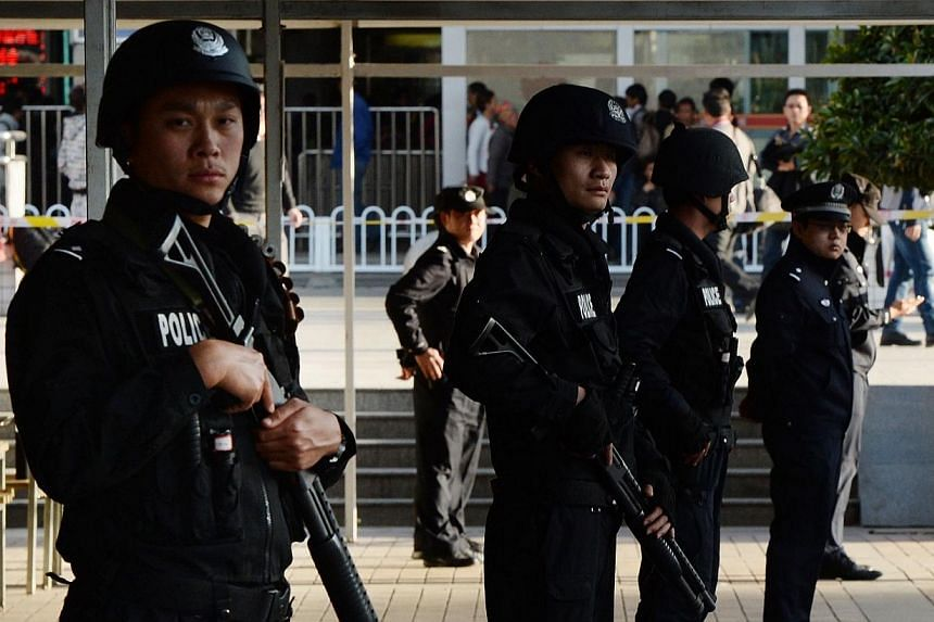Chinese police stand guard at the scene of an attack at the main train station in Kunming, Yunnan province on March 2, 2014. Defiant residents of the Chinese city that saw a mass stabbing queued to give blood on Monday, March 3, 2014, while others ve