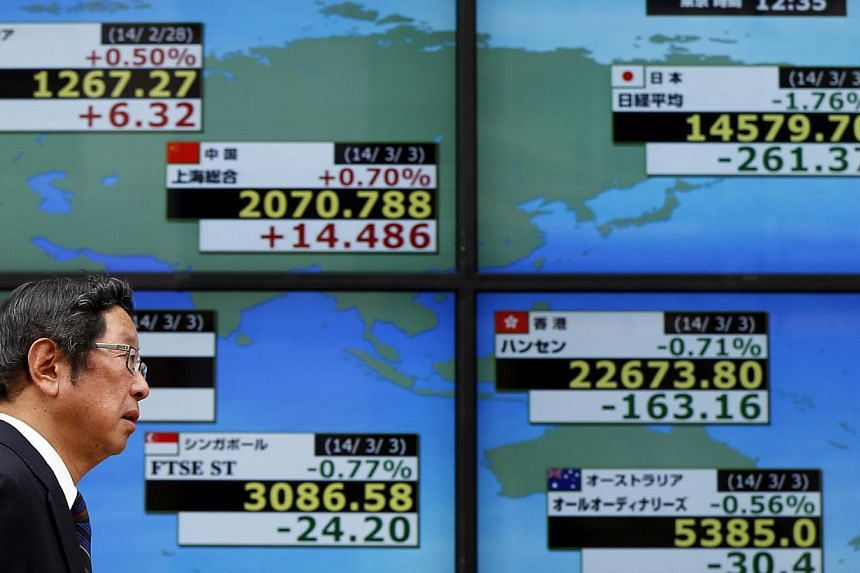 A man walks past at an electronic board displaying various countries' stock market indices outside a brokerage in Tokyo on March 3, 2014. -- PHOTO: REUTERS