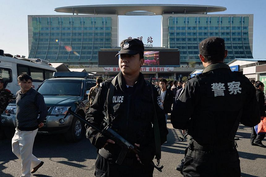 Chinese paramilitary police stand guard outside the scene of the terror attack at the main train station in Kunming, Yunnan Province, on March 3, 2014.Chinese police have caught three suspects in a railway station attack that left 29 people dea