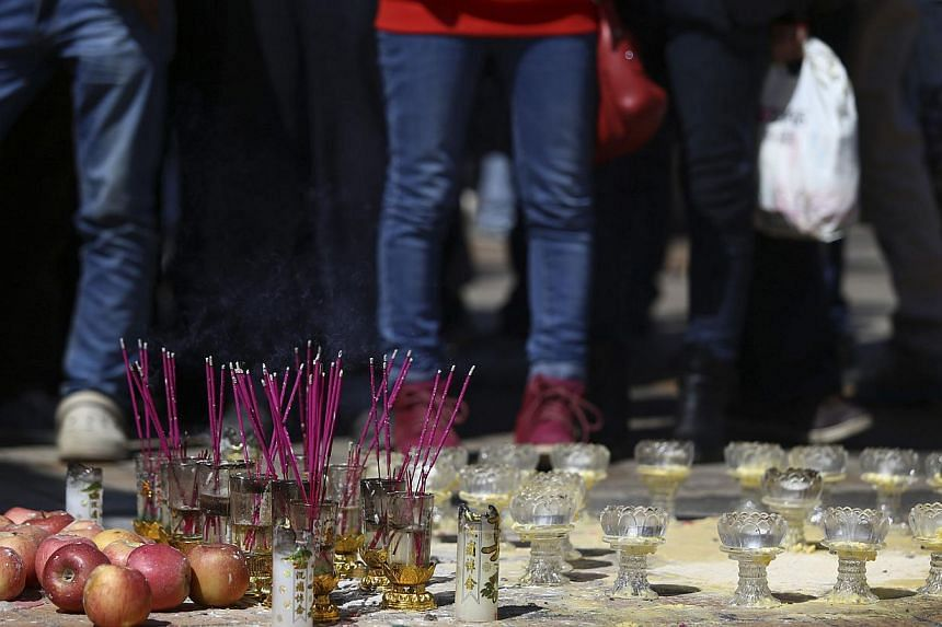 Apples, burning incenses and candle holders are seen on the floor as people pay tributes to the victims of a knife attack at Kunming railway station in Kunming, Yunnan province, on March 3, 2014. Defiant residents of the Chinese city where 29 people