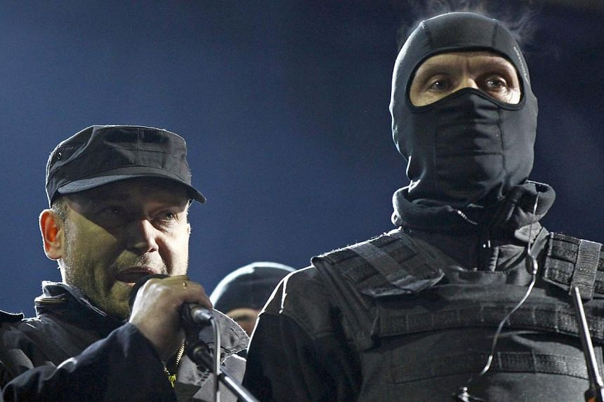 Dmytro Yarosh (left), a leader of the Right Sector movement, addresses during a rally in central Independence Square in Kiev, on Feb 21, 2014. Russia on Monday, March 3, 2014, said it was investigating the leader of a Ukrainian far-right group that c
