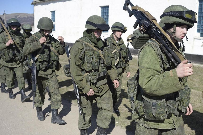 Armed men in military armed block access to a Ukrainian border guards base not far from the village of Perevalne near Simferopol, on March 3, 2014. Russian troops and military planes were flowing into Crimea on Monday in violation of accords between