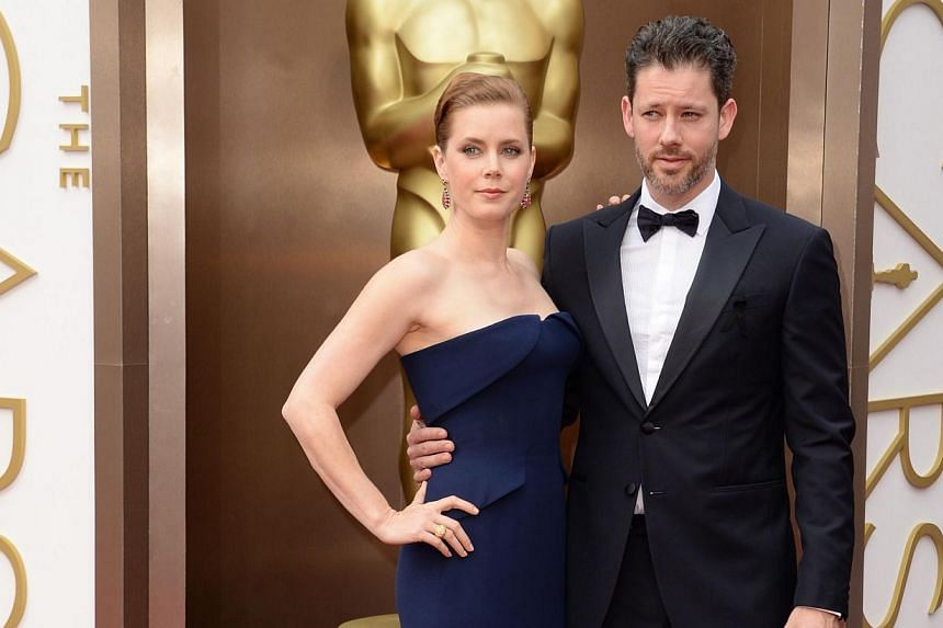 Best actress nominee for the film American Hustle, Amy Adams (left), and Darren Le Gallo arrive on the red carpet for the 86th Academy Awards in Hollywood, California, on March 2nd, 2014. -- PHOTO: AFP