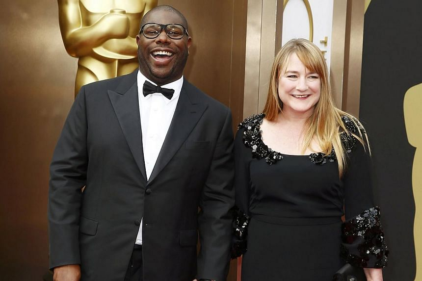 Steve McQueen, best director nominee for his film 12 Years A Slave, and partner Bianca Stigter arrive at the 86th Academy Awards in Hollywood, California on Mar 2, 2014. -- PHOTO: REUTERS