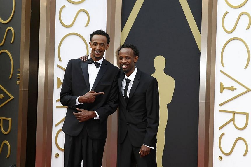 Barkhad Abdi (right), best supporting actor nominee for his role in the film Captain Phillips, arrives with actor Faysal Ahmed at the 86th Academy Awards in Hollywood, California, on Mar 2, 2014. -- PHOTO: REUTERS
