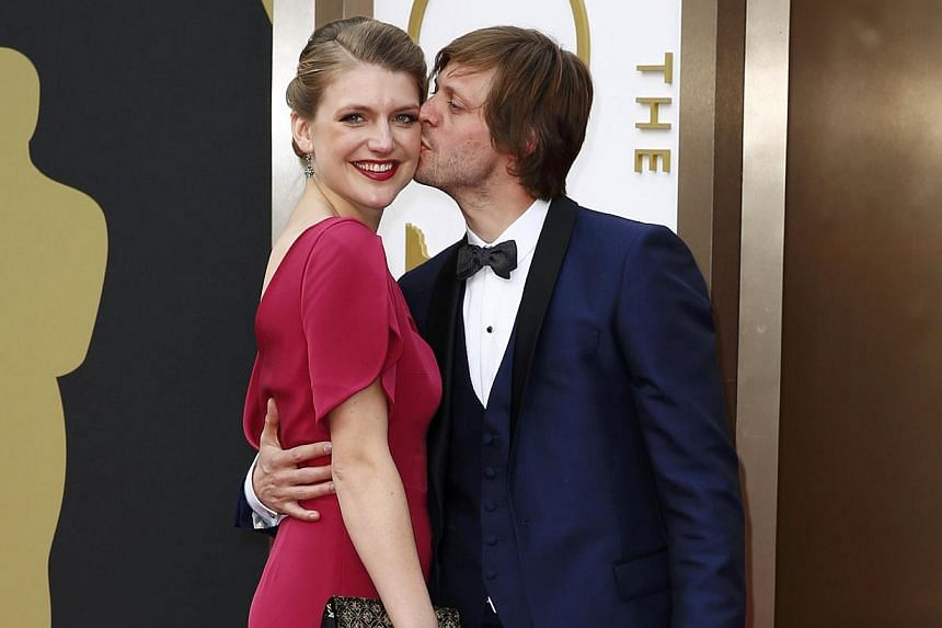 Felix Van Groeningen (right), director of Belgian film The Broken Circle Breakdown, and the film's star, Veerle Baetens, kiss on arrival at the 86th Academy Awards in Hollywood, California, on Mar 2, 2014. -- PHOTO: REUTERS