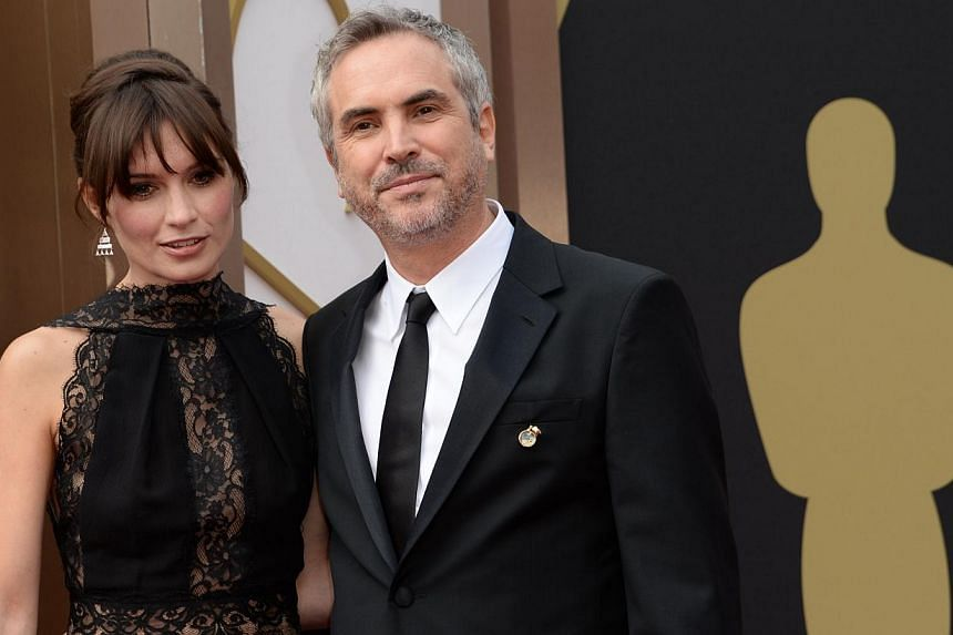Nominee for best director for the film Gravity, Alfonso Cuarón (right), and Sheherezade Goldsmith arrive on the red carpet for the 86th Academy Awards in Hollywood, California, on Mar 2nd, 2014. -- PHOTO: AFP