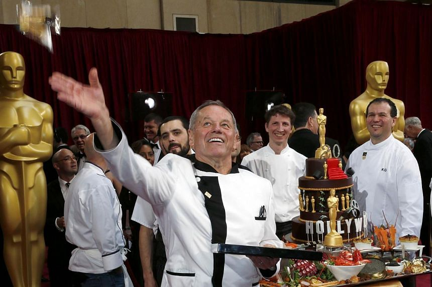 Celebrity chef Wolfgang Puck tosses one of his 2014 Oscars creations to the crowd as he shows them off with his teammates at the 86th Academy Awards in Hollywood, California, on Mar 2, 2014. -- PHOTO: REUTERS