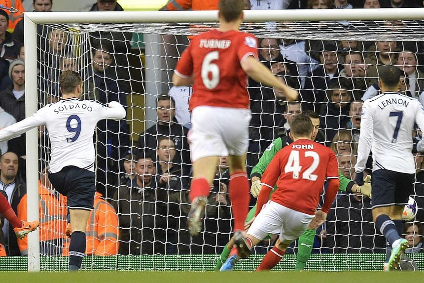 Tottenham Hotspur's Roberto Soldado (left) scores against Cardiff City during their English Premier League soccer match at White Hart Lane in London, on Mar 2, 2014. -- PHOTO: REUTERS