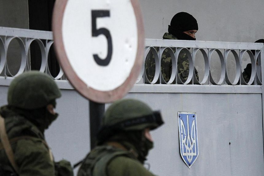 Military personnel, believed to be Russian servicemen, stand guard outside the territory of a Ukrainian military unit, with a Ukrainian serviceman (top right) seen in the background, in the village of Perevalnoye outside Simferopol on March 2, 2014.