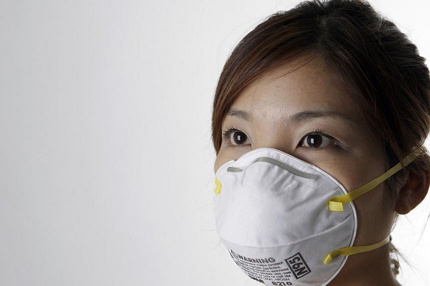 A woman wearing a N95 mask. Singapore has 16 million N95 face masks stockpiled in case the haze returns, the Government said in a Parliament session on Tuesday. -- MYPAPER FILE PHOTO: NEO XIAOBIN