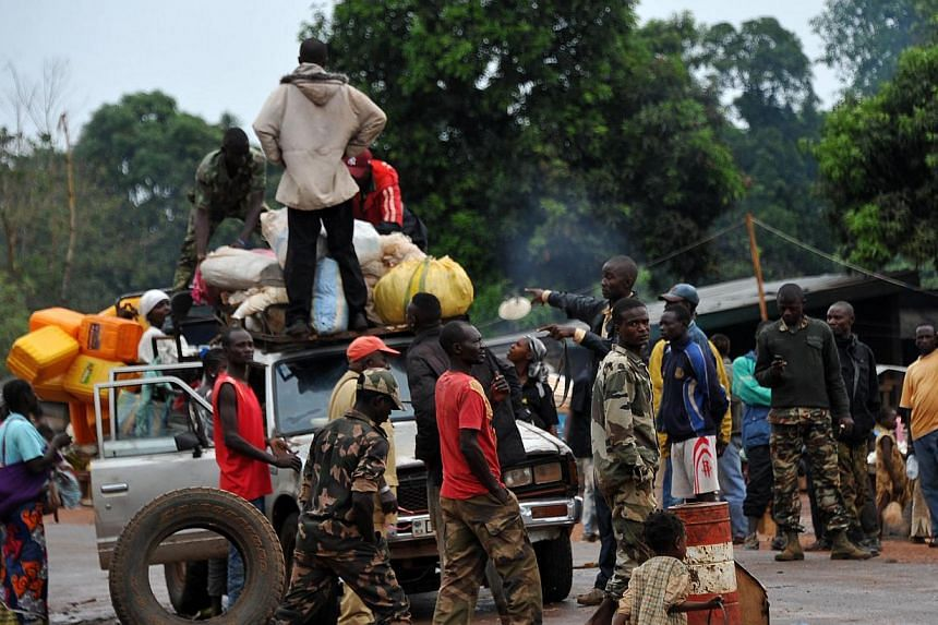 Members of the anti-Balaka Christian militia search a vehicle at a check-point in Pissa, 70 km south of Bangui, on March 3, 2014. United Nations Secretary General Ban Ki Moon recommended on March 3, 2014 deploying nearly 12,000 peacekeepers in Centra